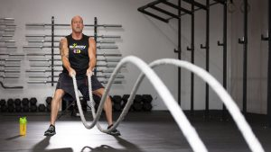 A man using battle ropes at the gym