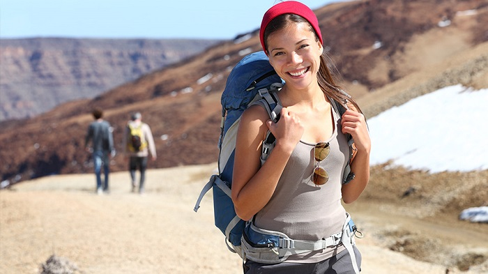 Woman hiking while wearing a blue backpack