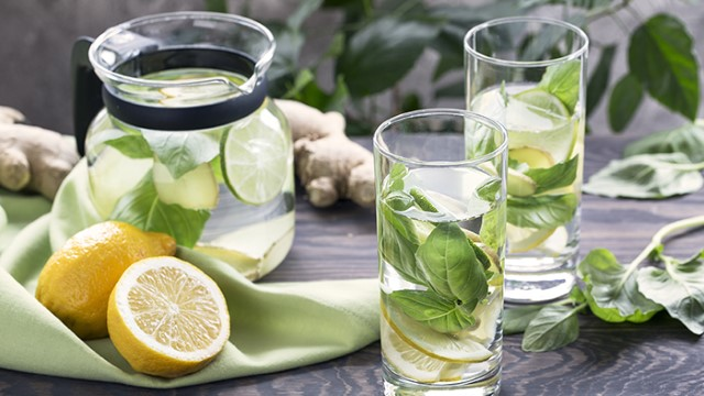 Pitcher of water with lime and mint with cut lemons and glasses of water