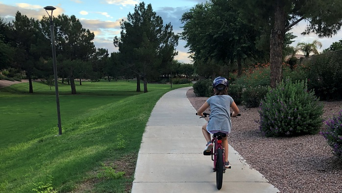 Child biking along a sidewalk in the park