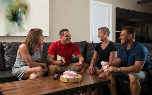 Four people sitting on a couch talking and enjoying Isagenix products