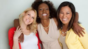 A group of three women hugging and smiling