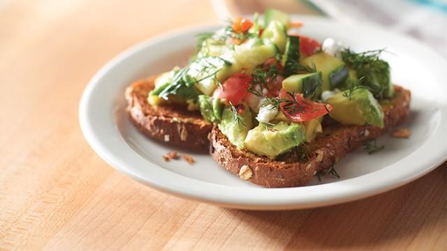 Slice of Greek avocado toast on a plate