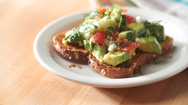 Slice of Greek avocado toast on a plate