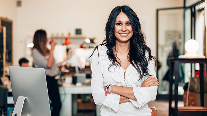 A woman in a white blouse stands in an office smiling and crossing her arms
