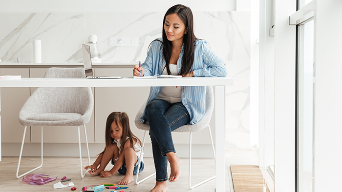 A mom works while her young daughter plays under the desk