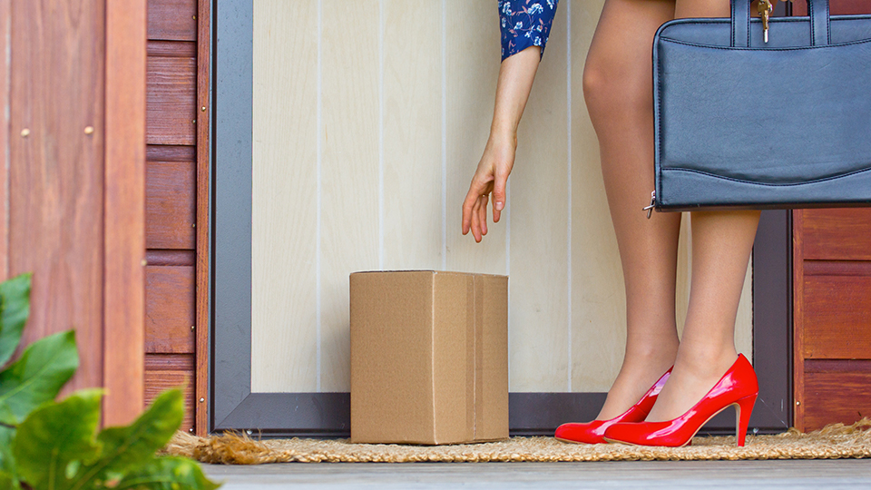 Woman in red heels reaches down for a package at the front door