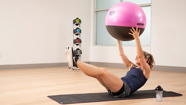 A woman lifting an exercise ball while doing a V-up