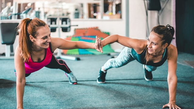 Two women doing pushups together and high-fiving