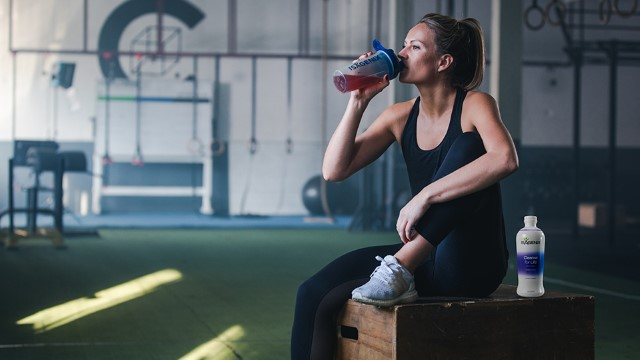 Woman drinking from an Isagenix shaker cup at the gym