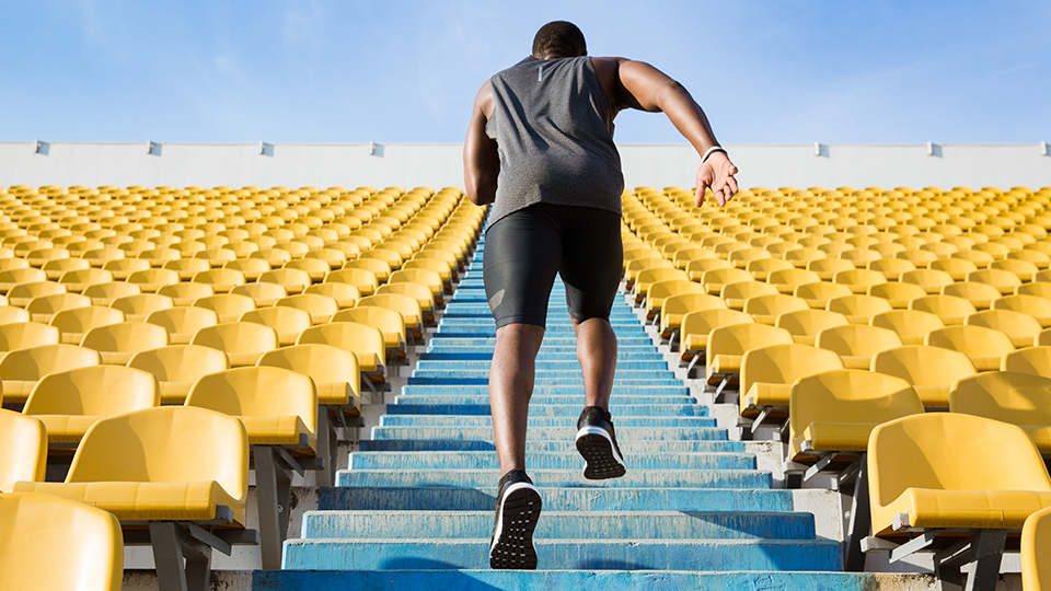 Man running up blue stairs surrounded by bright yellow stadium seats