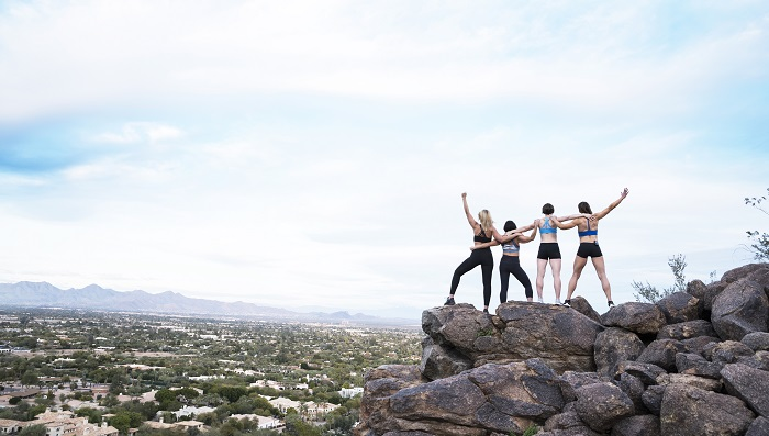 Group of IsaBody Challenge finalists standing on top of a mountain with their arms in the air