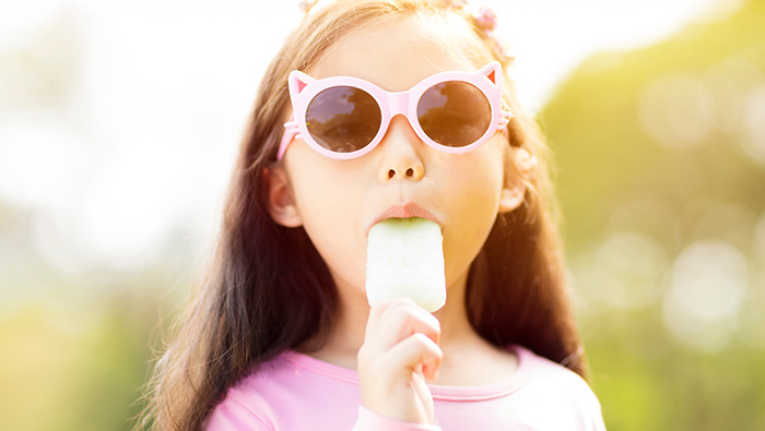 Girl eating popsicle.