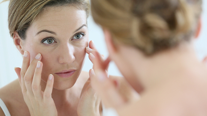 Woman examining her face in a mirror.