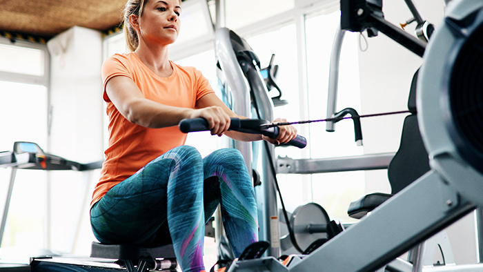 Young woman in fitness attire on a rowing machine.
