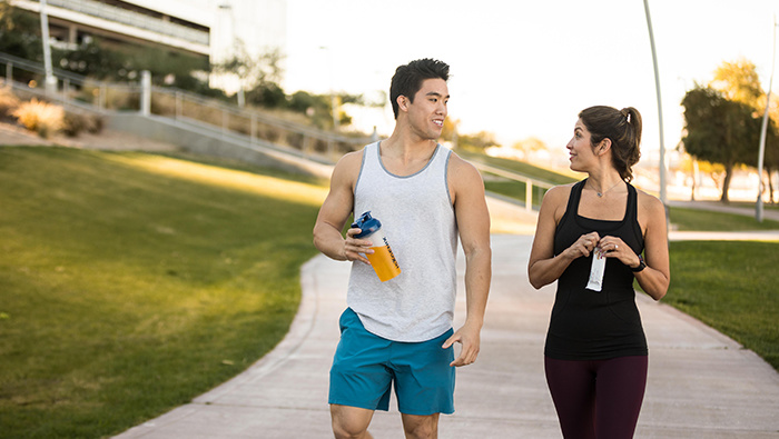 Man and woman talking while holding a bottle of liquid and opening a protein bar wrapper.