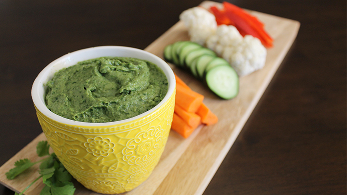A bowl of hummus on a board of carrots, cucumbers, cauliflower, and bell peppers.