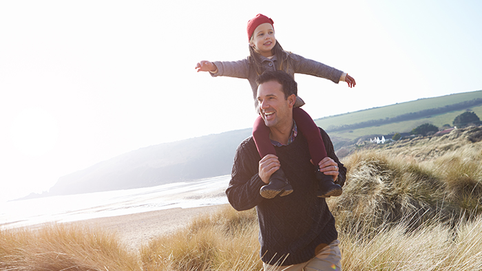 Father holds daughter on his shoulders by the beach