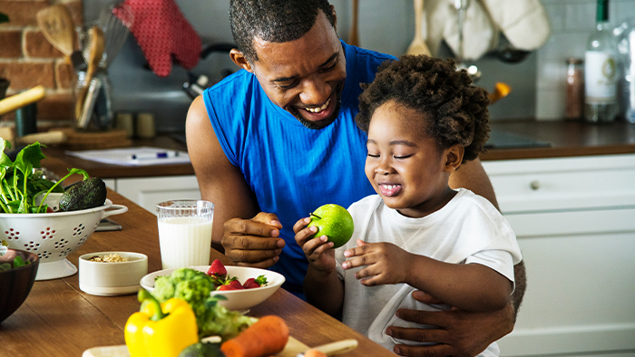 Father and child preparing fresh fruits and veggies in the kitchen