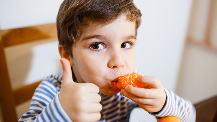 Young boy eating a tangerine while giving a thumbs-up.