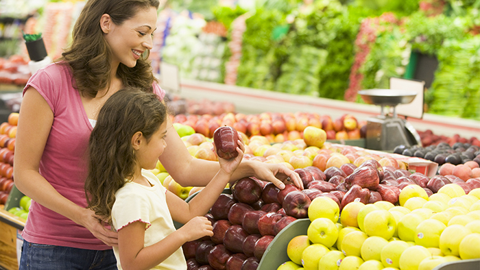 Mother and daughter grocery shopping and looking at apples.