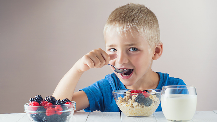 Young boy eating oatmeal, granola, and berries with a glass of milk on the side.