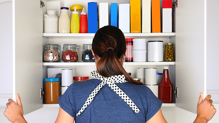 Back of woman, who is looking at her cabinet of groceries.