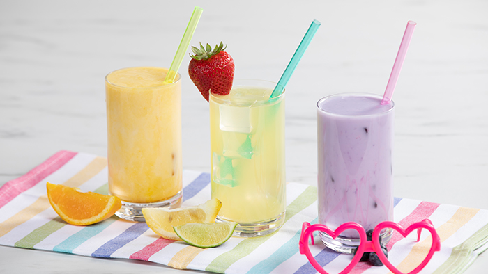 Three glasses of Lemon Lime, Orange, and Grape Hydrate Coolers with straws