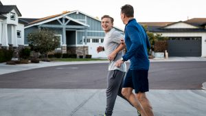 Father and adult son exercising on a neighborhood street