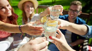 Five friends sit outside and clink glasses of water with orange slices in them