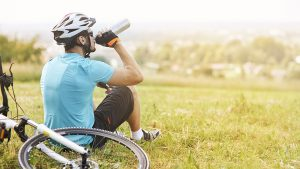 A man in bike riding gear sits on the grass and drinks water from a water bottle next to his bicycle