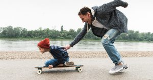 A dad pushing his kid on a skateboard by the water