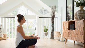 Woman doing yoga in bedroom