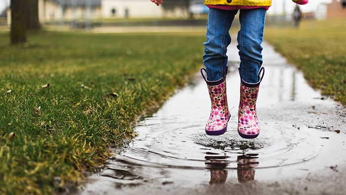 A close-up of a child's pink flower galoshes as they jump in a rain puddle