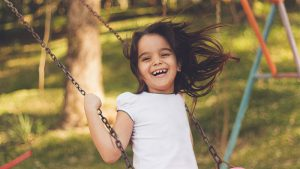 A little girl with brown hair smiling while swinging