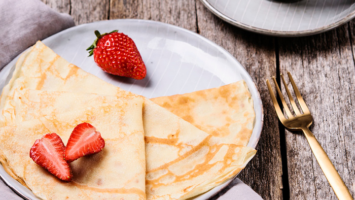 Plate with crepes and strawberries and a fork on the side