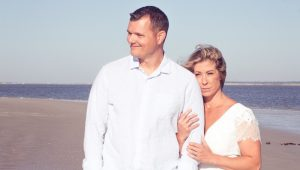 Christie Nix stands on the beach with her husband