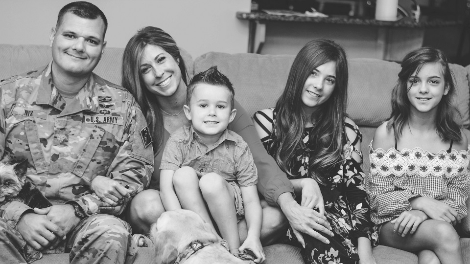 Christie Nix sitting on the couch with her family