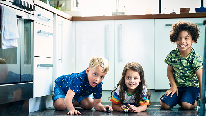 Three children playing in the kitchen
