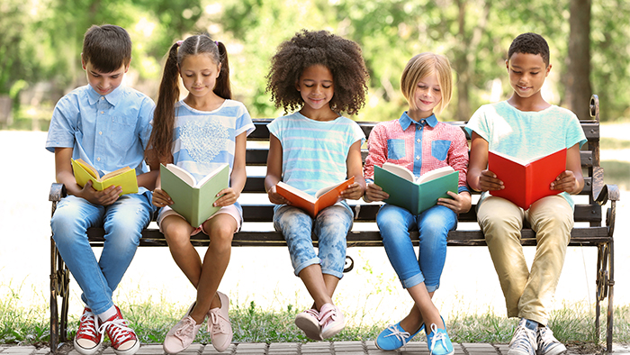 Children reading books on a bench