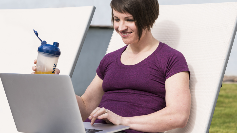 Woman working on laptop while drinking Isagenix AMPED Hydrate