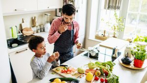Father and son cutting and eating fruits and vegetables