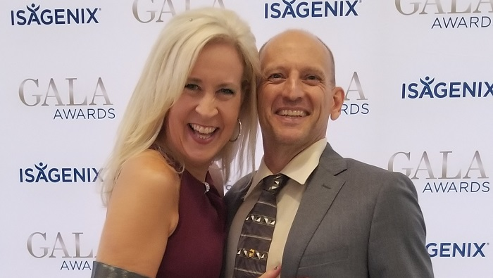 Husband and wife Brent and Tracey Shaw smiling in front of the Isagenix Gala Awards wall
