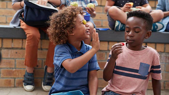 Boy with a grape against his closed eye reaching out for a high-five from another boy holding a piece of fruit