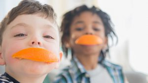 Two boys with orange peels over their mouths