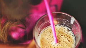 Female holding a glass with a smoothie and a straw in it