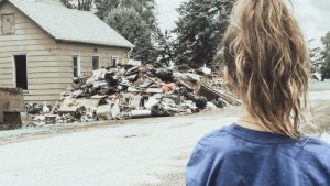 A young girl looks at a pile of trash and debris