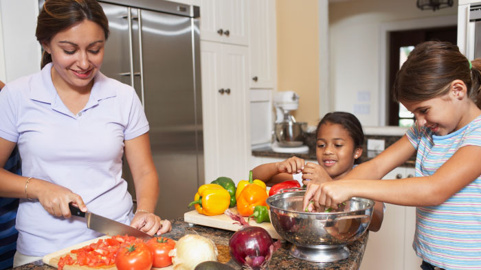 Two girls preparing vegetables in the kitchen with their mother