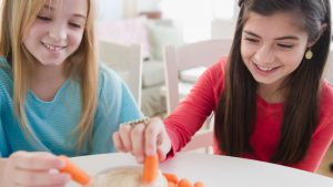 Two girls dunking carrots in dip