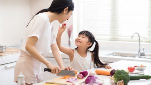 Young girl feeding her mother a grape tomato while they chop vegetables in the kitchen